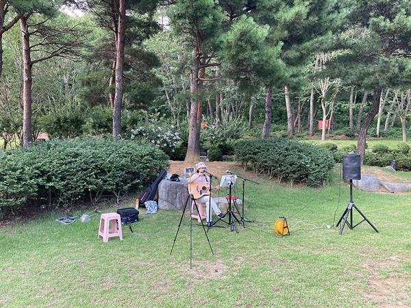 경주 흥무공원 녹지대에서 혼자 기타 연습에 열중하는 시민 모습