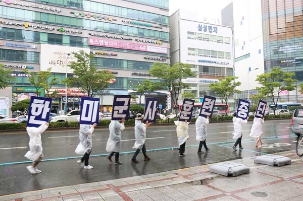 참가자들이 <한미군사훈련중단>이라고 적힌 피켓을 들고 행진하고 있다.