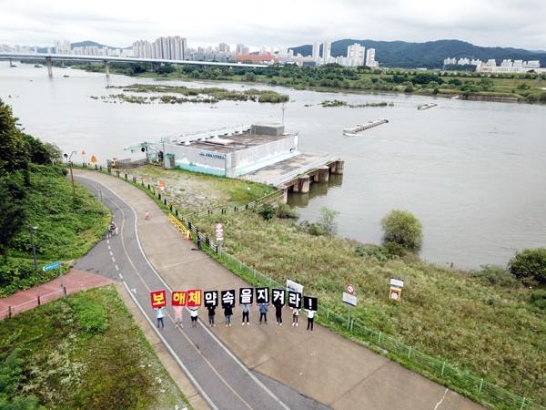 """환경시민단체들은 28일 환경부 앞에서 4대강재자연화 촉구 기자회견을 마친 뒤에 세종보 앞에서 """"보 해체""""를 촉구하는 퍼포먼스를 벌였다."""