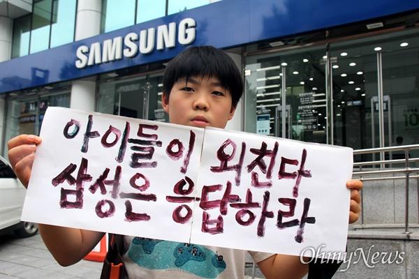 """경남기후위기비상행동은 7월 29일 삼성전자서비스 마산센터 앞에서 기자회견을 열어 """"삼성의 석탄화력발전 투자 중단되어야 한다""""고 했고, 마산가포초등학교 박지호(6년)군이 손팻말을 들고 서 있다."""
