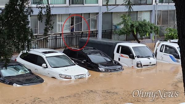밤새 집중호우가 내린 대전 서구 정림동의 한 아파트 30일 오전 상황. 아파트 출입구까지 물이 차올라 1층 거주민이 걱정스럽게 지켜보고 있다.