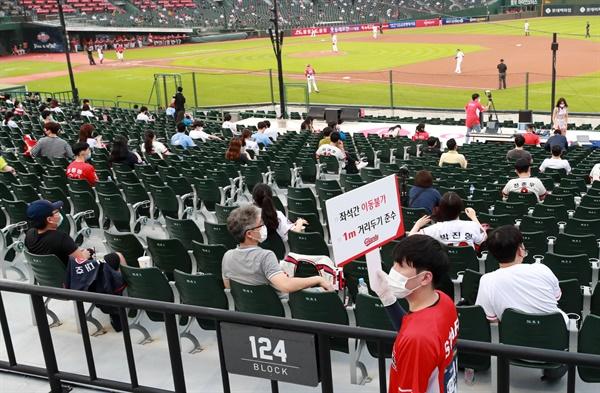 지난달 31일 오후 부산 사직구장에서 열린 KIA 타이거즈와 롯데 자이언츠 경기에서 롯데 자이언츠 관계자들이 거리두기를 안내하고 있다.