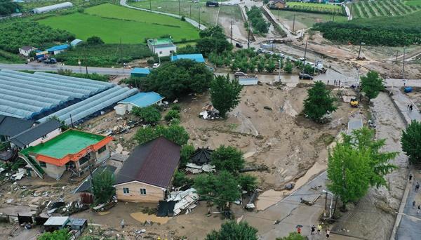 많은 비가 내려 2일 오전 둑 일부가 무너진 경기 이천시 산양저수지 부근 마을이 토사로 덮여 있다.