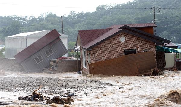 2일 오후 밤사이 많은 비가 내린 충북 충주시 산척면 불어난 하천변 주택이 기울어져 있다.