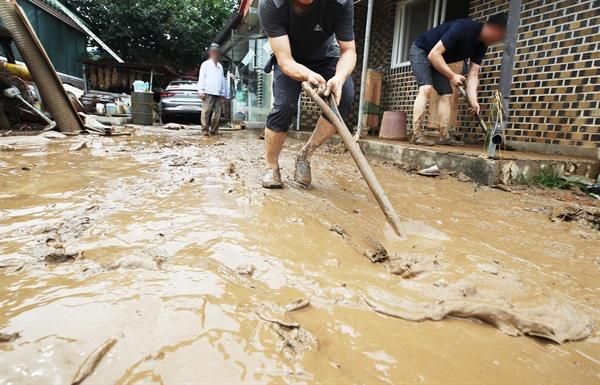밤사이 내린 집중호우로 둑이 무너진 경기도 이천시 산양저수지 부근 마을에서 2일 오후 주민들이 마당에 쌓인 토사를 치우고 있다.
