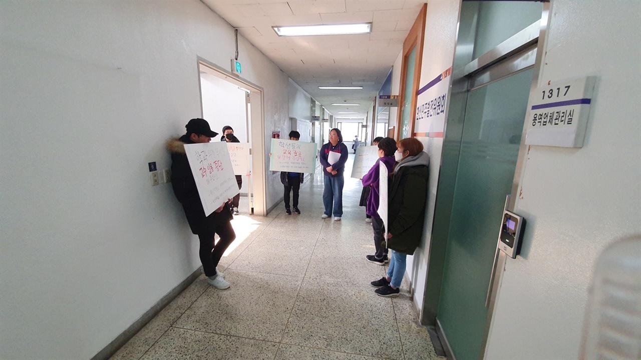교수임용 중단을 위해 회의실 앞에서 피켓팅과 성명문 배포 등의 선전 활동을 하고 있다.