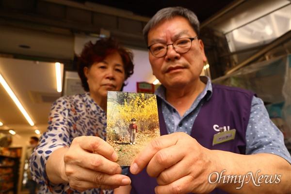 군사망피해자 고 이철구 일병의 어린시절 사진을 들고 있는 아버지 이현규씨와 어머니 임승민씨.