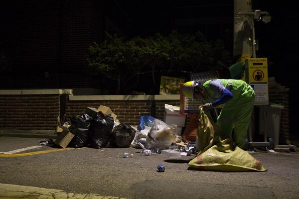 청소노동자가 널브러진 쓰레기들을 정리하고 있다.
