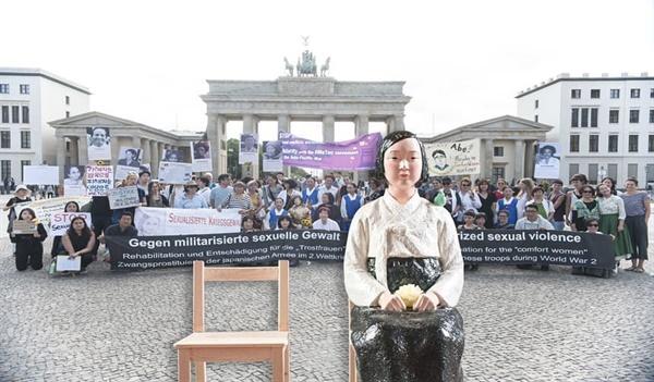 """작년 8월 14일 세계 일본군 위안부 기림일, 브란덴부르크 문 앞에서 열린 시위. 베를린의 여러 여성단체들과 """"용희"""" 라는 이름의 소녀상도 집회에 함께 했다."""