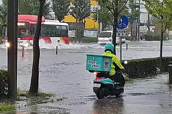 7일 광주 지역에 내린 폭우로 인해 곳곳이 침수된 모습. 광주 서구 동천동의 한 도로를 배달라이더가 위태롭게 지나고 있다.