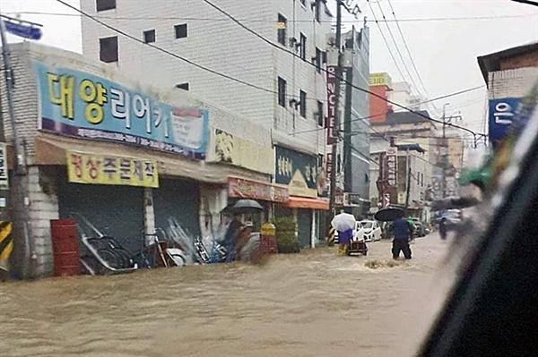 7일 광주 지역에 내린 폭우로 인해 곳곳이 침수된 모습. 허벅지까지 물이 찬 광주 서구 양동의 도로를 시민들이 지나고 있다.
