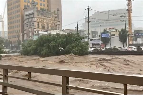 7일 광주 지역에 내린 폭우로 인해 곳곳이 침수된 모습. 광주 동구 호남동 인근의 광주천 물이 곧 넘칠듯 흐르고 있다.