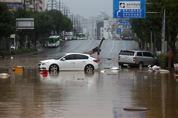 집중호우가 내린 8일 오전 광주 북구 신안교 부근 도로를 지나던 차량이 침수로 멈춰서 있다.