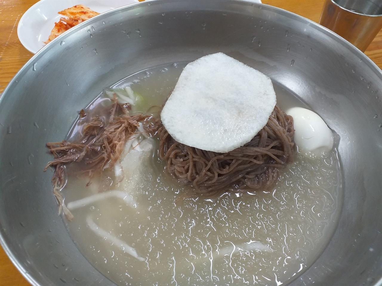 정통 황해도식 냉면 뽀얀 육수에 양이 압도적이다. 면 옆의 갈색물체는 육수를 내린 양지고기다. 실처럼 얇에 찢어 고명으로 올린다.