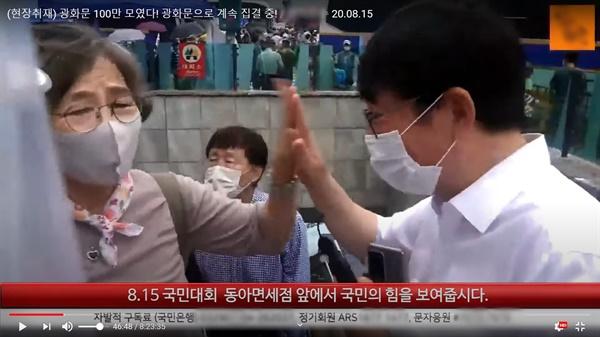 지난 15일(광복절) 광화문 집회를 생중계한 한 유튜브 채널이 중계 도중 집회 참석자와 손바닥을 부딪히며 인사하고 있다.