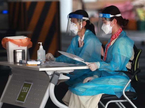 20일 오후 부산 사상구보건소에 마련된 선별진료소에서 보건소 의료진이 부채로 더위를 식히고 있다.