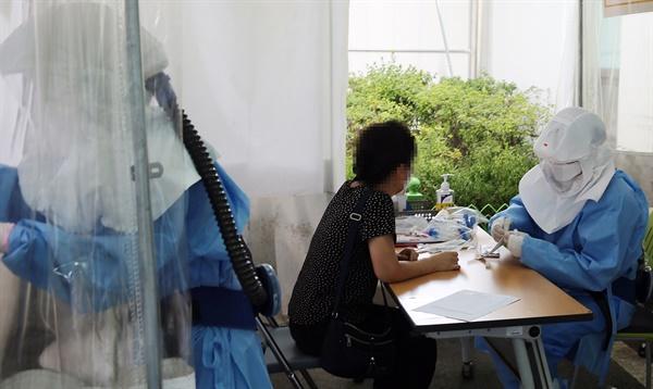 전국 곳곳에 폭염특보가 내려진 20일 대전 서구 건양대병원 선별진료소에서 의료진이 신종 코로나바이러스 감염증(코로나19) 검사를 위한 검체 채취를 하고 있다.