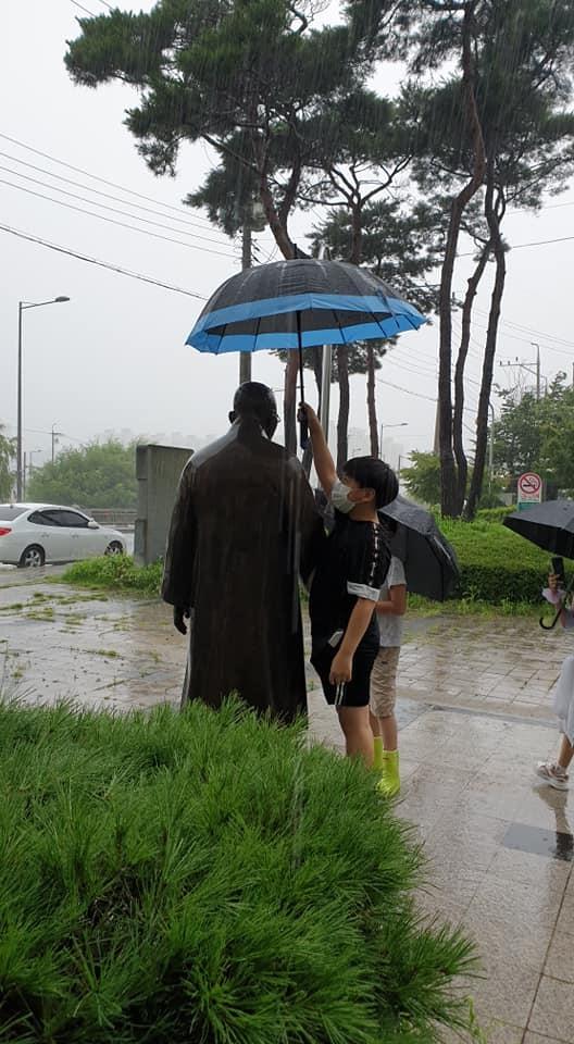 비맞는 김구선생 동상에 우산을 씌우는 학생