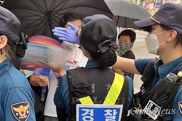 21일 오전 기자회견을 앞둔 사랑제일교회 인근의 모습. 신도로 보이는 한 여성이 마스크를 제대로 착용하지 않은 채 경찰에 폭언을 쏟아내며 부채질을 하자, 경찰이 이를 말리고 있다.