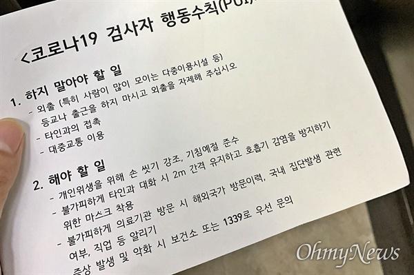 23일 코로나19 선별진료소인 서울의 한 보건소의 모습. 검사 후 보건소 측에서 나눠준 검사자 행동수칙 안내문.