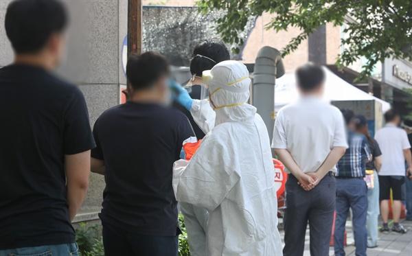 24일 오전 대전시 서구 보건소 앞에서 코로나19 진단검사를 받으려는 시민들이 검사에 앞서 발열 체크를 하고 있다.