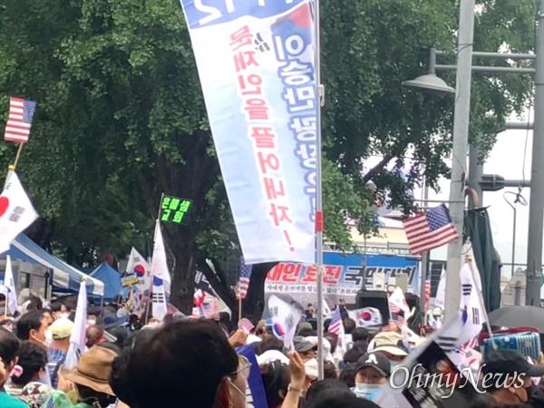 지난 8월 15일 보수 성향 단체 '일파만파'가 서울 광화문 동화면세점 앞에서 주최한 집회 근처에 참가자들이 모여 태극기를 흔들고 있다.
