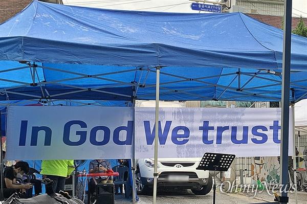 2일 오전 전광훈 목사가 기자회견을 진행한 사랑제일교회 앞 현장에는 'in god we trust(우리는 하느님을 믿어요)'라고 적힌 현수막이 붙어 있었다. 'in god we trust'는 미국의 국가 표어로 화폐에도 새겨져 있는 문구다.