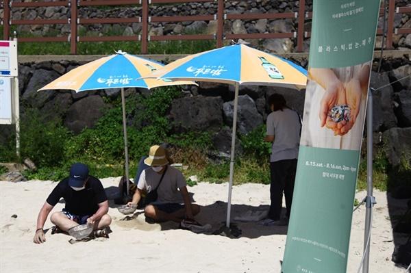 시민들이 모래 해변에서 미세 플라스틱을 줍고 있다.
