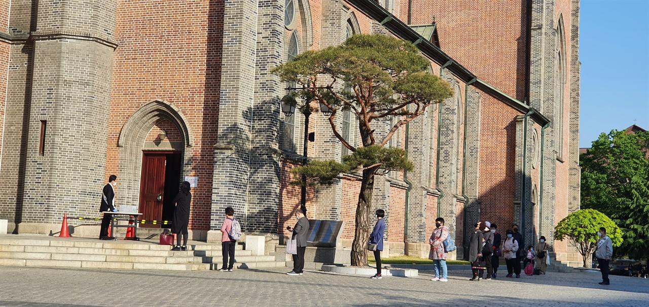 """""""성전에서도 사회적 거리두기"""" 지난 5월 5일 명동성당에서 미사를 드리기 위해 온 신자들이 성전에 입장하기 전 사회적 거리두기를 하며 줄을 서서 차례를 기다리고 있다."""
