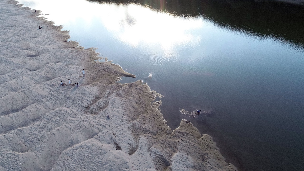 강변 모래톱에는 많은 시민이 찾아 휴식을 취하고 아이들은 모래 장난에 여념이 없습니다.