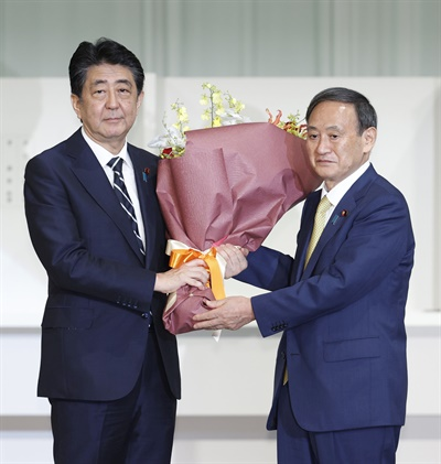 스가 요시히데(菅義偉) 일본 관방장관이 14일 도쿄 한 호텔에서 열린 집권 자민당 총재 선거에서 경쟁 후보들을 압도적인 표 차로 제치고 총재에 당선됐다. 사진은 14일 총재 경선이 끝난 뒤 아베 신조(安倍晋三) 총리로부터 축하 꽃다발을 받는 스가 신임 자민당 총재.