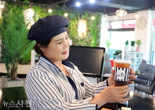 직접 내린 커피를 들고 있는 김경자 바리스타.