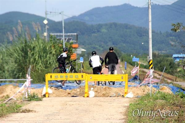 8월 9일 새벽 낙동강 합천창녕보 좌안 상류에 있는 둑이 터져 복구공사가 진행되는 가운데, 자전거를 탄 사람들이 이동에 불편을 겪고 있다.