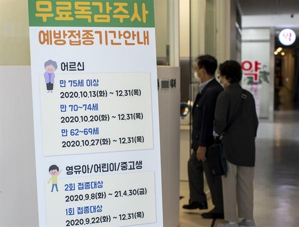 """22일 오전 서울의 한 병원에 무료독감주사 관련 안내문이 세워져 있다. 질병관리청은 21일 보도자료를 통해 """"인플루엔자 조달 계약 업체의 유통 과정에서 문제점을 발견해 오늘부터 시작되는 국가 인플루엔자 예방접종 사업을 일시 중단할 계획""""이라고 밝혔다"""