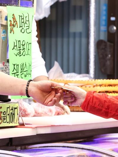 추석을 앞둔 지난 24일 오후 서울 성북구 장위전통시장을 찾은 시민이 계산을 하고 있다.