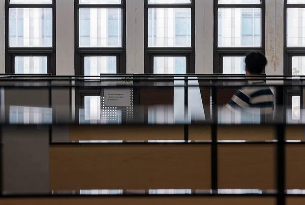 16일 서울 서대문구 신촌동 연세대학교 학생회관 내 취업 카페에서 자습 중인 한 학생이 채용 상담 부스 앞을 지나고 있다.