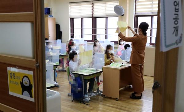 마스크 쓰고 수업하는 초등학생들 수도권 지역 유치원과 초·중·고교의 등교수업이 재개된 21일 서울 강동구 한산초등학교 학생들이 1교시 수업을 하고 있다.
