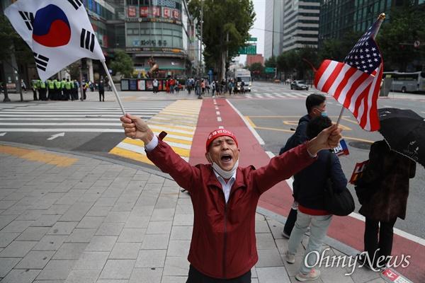 개천절인 3일 서울 도심에서 보수극우단체들이 문재인 정권 규탄 집회를 예고한 가운데, 종로1가에서 한 시민이 태극기와 성조기를 흔들며 문 대통령 규탄 구호를 외치고 있다.