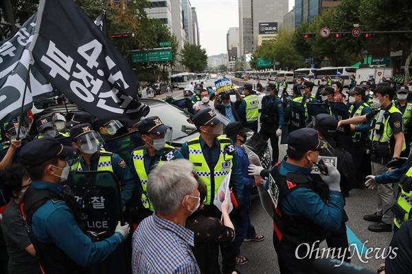 개천절인 3일 서울 도심에서 보수극우단체들이 문재인 정권 규탄 집회를 예고한 가운데, 종로1가에서 4.15부정선거 규탄 차량시위를 통제하는 경찰에 맞서 보수단체 회원들이 몸싸움을 벌이고 있다.