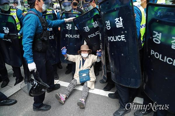 개천절인 3일 서울 도심에서 보수극우단체들이 문재인 정권 규탄 집회를 예고한 가운데, 종로1가에 한 시민이 해산을 요구하는 경찰에 맞서 몸싸움을 벌이다 바닥에 주저앉아 있다.
