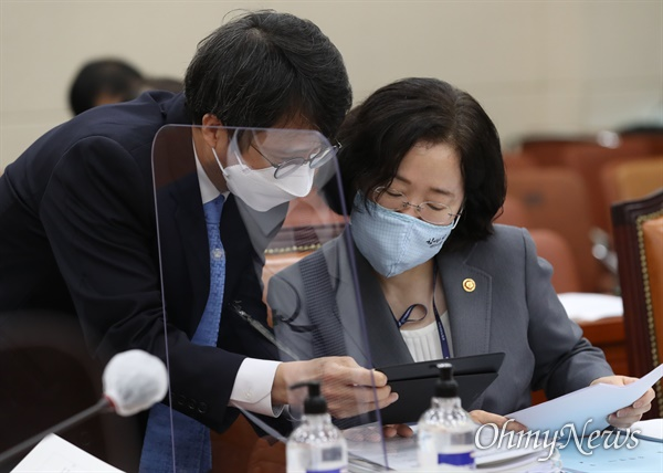 조성욱 공정거래위원장이 8일 오전 국회 정무위원회에서 열린 국정감사에 출석해 관계자와 회의 자료를 살펴보고 있다.