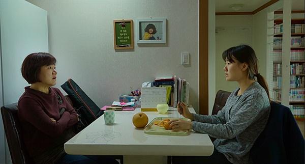 """디어 마이 지니어스 막내의 교육을 두고 테이블에 마주앉은 엄마와 맏언니. 마치 영화는 관객에게 """"당신이라면 어떻게 말할 건가요""""하고 묻는 듯하다."""