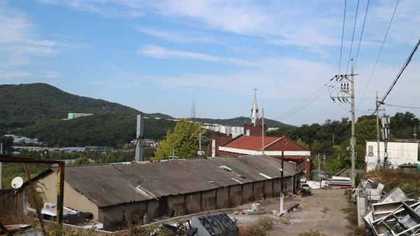 헌인마을, 한센인 정착촌의 옛 흔적 예전에는 축사였을 곳에 가구 공장들이 들어섰다. 교회 탑 너머 멀리 롯데타워가 신기루처럼 보인다.