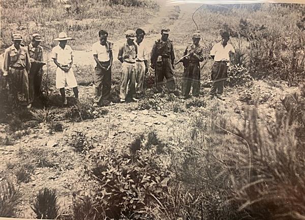 [발굴사진] 1950년 대전 골령골에서 군경이 민간인을 학살한 직후 현장 모습이 담긴 사진이 확인됐다. 총을 멘 북한군 5명과 마을주민으로 보이는 4명이 한 줄로 늘어서 시체가 묻힌 구덩이를 응시하고 있다.1950년 7월 또는 8월, 대전을 점령한 북한군과 함께 골령골 현장을 방문한 영국 <데일리 워커>의 앨런 위닝턴 기자가 찍은 사진이다.