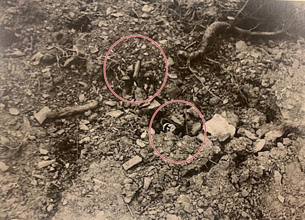 """[발굴사진] 희생자 유해(위 붉은 원안)로 보인다. 위닝턴 기자는 기사에서 """"땅에 버려진 빈 담배 갑들과 놓여 있는 수천 개의 탄약통은 모두 미제였다. 미군 장교들이 한국군 장교들과 매일 지프를 타고 와서 학살을 감독했다""""며 """"이런 살인극은 미군의 지시에 의해 이루어진 것""""이라고 보도했다. 1950년 7월 또는 8월, 대전을 점령한 북한군과 함께 골령골 현장을 방문한 영국 <데일리 워커>의 앨런 위닝턴 기자가 찍었다."""