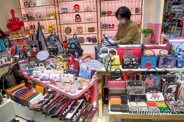 가방가게를 운영하는 이정현 두타몰 상인 비상대책위원장이 상품을 진열하며 손님을 기다리고 있다.