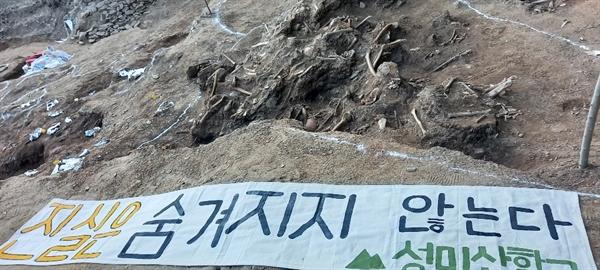 성미산학교 학생 12명이 대전 골령골에서 유해발굴 봉사활동을 마친 후 희생자 유해 앞에 '진실은 숨겨지지 않는다'는 천 글씨를 펼쳤다.