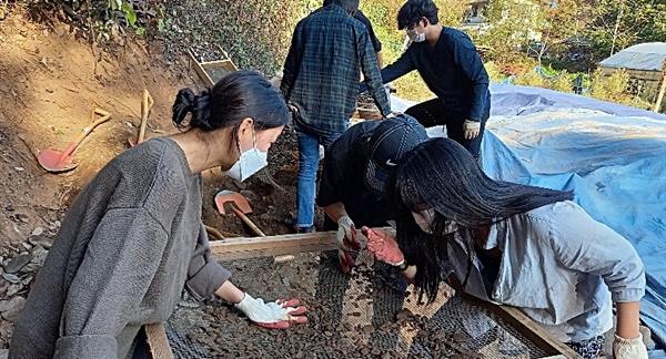 20일, 성미산학교 11학년과 12학년(고등학교 2, 3학년 과정) 학생들이 대전 골령골에서 흙을 채에 거르며 유해 파편을 찾고 있다.
