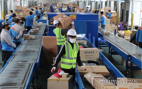 21일 서울 서초구 CJ대한통운 강남2지사 터미널 택배분류 작업장에서 택배기사들이 택배 분류 작업을 하고 있다.