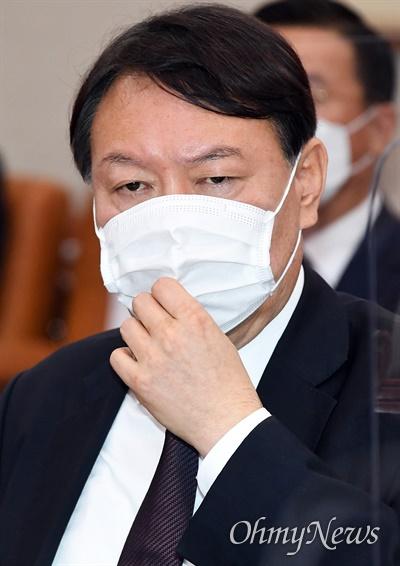 윤석열 검찰총장이 22일 국회에서 열린 법제사법위원회 대검찰청 국정감사에서 마스크를 만지고 있다.